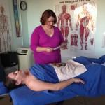 Ariel prepares to do anterior body Hot Stone Massage.